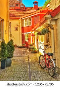 TALLINN, ESTONIA, MAY 2017. Red bicycle on the street of Old Town. Colorful houses and stone road, plants and flowers. Mobile photo with HDR effect.