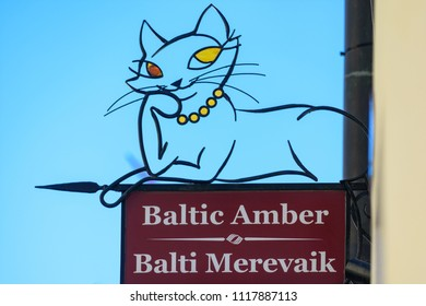 Tallinn, Estonia - May 30 2018: A sign outside a Baltic Amber shop in Tallinn, Estonia, displays a wrought iron cat silhouette with amber eyes