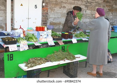 TALLINN ESTONIA - May 5. Elderly Russian people are buying, selling and shopping at nostalgic farmers market with Russian words for herbs and vegetables at the vintage Russian Market on May 5, 2015.