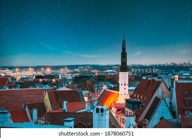Tallinn, Estonia. Night Starry Sky Above Traditional Old Architecture Skyline In Old Town. Church Of Holy Ghost Or Holy Spirit In Winter Evening. Landmark UNESCO Heritage Site. Altered Sky Stars.