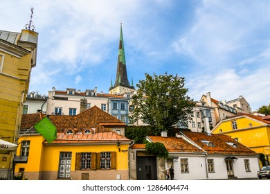 Tallinn, Estonia - September 10 2018: The spire of the medieval St. Olaf's Church rises above the village lining the ancient walls of the Baltic city of Tallinn, Estonia.
