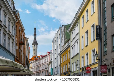 Tallinn, Estonia - September 10 2018: The tower and spire of the Tallinn Town Hall building rises above a typical medieval, picturesque street full of cafes and hotels in Old Town Tallinn Estonia.