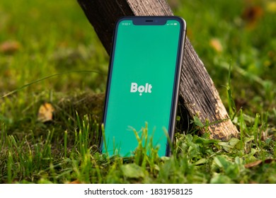 Tallinn / Estonia - September 28, 2020: Black iphone with logo of Bolt application on the screen. Green grass background. Can be used as illustrative for marketing or business concept
