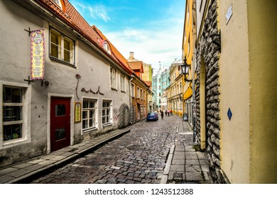 Tallinn, Estonia - September 9 2018: Tourists walk down a picturesque cobblestone street in a residential and business area of the medieval old town in Tallinn, Estonia