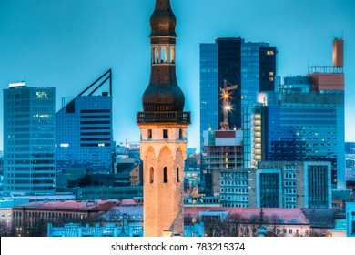 Tallinn, Estonia. Tower Of Town Hall On Background With Modern Urban Skyscrapers. City Centre Architecture.