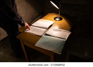 TALLINN/ESTONIA - SEPT. 6, 2020: A dramatic, atmospheric, low-key, dark photo of a man's hand on a historic typed KGB document on a desk with desktop light in the KGB Museum in old town Tallinn.