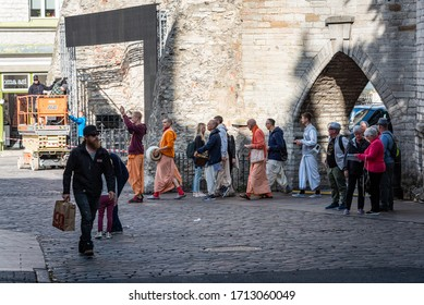 TALLINN/ESTONIA - SEPT. 6, 2020: A group of Hare Krishna followers sing and walk through the Viru gate in the medieval old town.