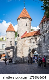 TALLINN/ESTONIA - SEPT. 6, 2020: A vertical orientation photo of tourists entering medieval old town through one of its original turreted gates.
