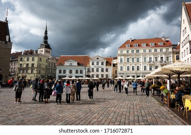 TALLINN/ESTONIA - SEPT. 6, 2020: View of the historic, cobblestone Town Hall Square (Raekoja Plats) with tourists in the medieval old-town Tallinn with a stormy, overcast sky.