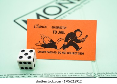 Tallinn/Estonia-04.11.2020: Monopoly board game. Family fun activity during corona outbreak.Go directly to jail. Community chest card. Orange monopoly card. Dice in corner. Criminal 's path