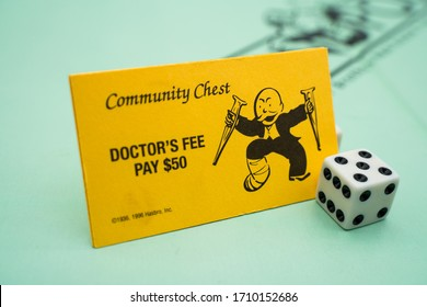 Tallinn/Estonia-04.11.2020: Monopoly board game. Family fun activity during corona outbreak. Doctor's fee, pay hospital 100$. Community chest card. Yellow monopoly card. Dice in corner.