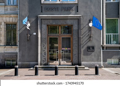 Tallinn/Estonia-05.20.2020: Estonian National Bank main building located in the city center. National and European flag in front next to the main entrance. Old looking building. Strong construction