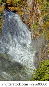 The Tallulah River gorge in the fall with rock walls and a pool at the bottom of the waterfall.