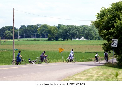 Talmage, PA, USA - June 24, 2018: An Amish family on bicycles heads home after church services in Lancaster County, PA.