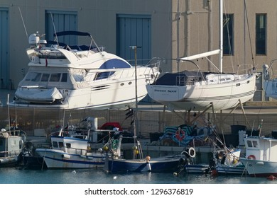 taly, Sicily, Mediterranean sea, Marina di Ragusa; 27 January 2019, wooden fishing boats and luxury yachts in the port - EDITORIAL
