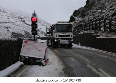 Tal-y-llyn, Gwynedd, Wales, UK.  February 10, 2020.  A gritter lorry approaching on a bleak, cold, snowy mountain pass.