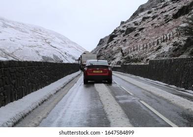 Tal-y-llyn, Gwynedd, Wales, UK.  February 10, 2020.  Vehicles queued on the bleak, cold, snowy pass.