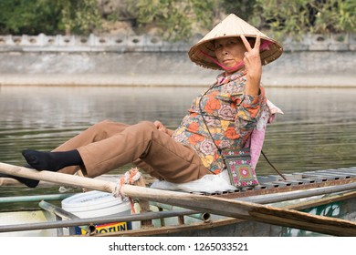Tam Coc, Nihn Binh, Vietnam - 12/2/2018:  Woman towing her sampan with her feet in the Tam Coc river valley.