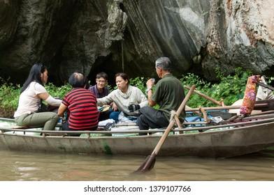 Tam Coc, Ninh Binh Province, Vietnam - April 25th, 2016 - Vietnamese merchandise sellers in rowboats along Tam Coc stream in Vietnam.