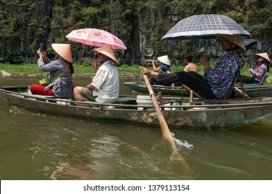 Tam Coc, Ninh Binh Province, Vietnam - April 25th, 2016 - Rowers and tourists traveling by boat along Tam Coc river.