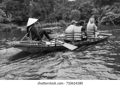 Tam Coc, Ninh Binh, Vietnam - April 13, 2017: Black and white, The tourists are travelling by boat in Ngo Dong river