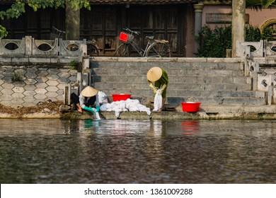Tam Coc River, Ninh Binh/Vietnam - 03/10/2019: Vietnamese women washing white bed linens in the Tam Coc River