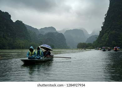 Tam Coc, Vietnam - December 09, 2018: Boatman with tourists is swimming on the boat at Tam Coc, Ninh Binh