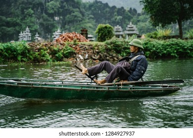 Tam Coc, Vietnam - December 09, 2018: Boatman is swimming on the boat at Tam Coc, Ninh Binh