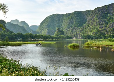 Tam Coc, Vietnam - June 8, 2019: Tourist taking boat tour through tam coc. Landscape with mountains and Rice field in Tam Coc Vietnam.
