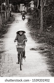 Tam Coc,Ninh Binh,Vietnam 5 feb 2018:one woman going by bicycle in Tam Coc city,Vietnam.Vietnamese women ride bicycle on countryside road.Bike is popular transport at Vietnam.Black and white photo