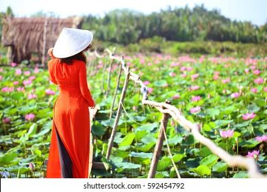 Tam Da lotus lake, Ho Chi Minh city, Vietnam - February27, 2017: Vietnamese woman wearing red traditional clothing (Ao dai) on footbridge at lotus lake