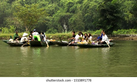 Tam Cốc River, Ninh Binh / Vietnam - October 16 2018: Women merchants on boat showing their merchandise to tourists. These merchants work very hard in these part of the river to earn on a daily basis.