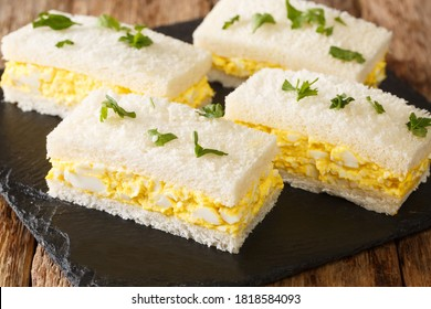 Tamago Sando is a very humble snack, modest, low maintenance and very convenient. The Japanese Egg Sandwich close-up on a slate board on the table. Horizontal