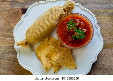 Tamale served with hot tomato sauce and tortillas on Wooden tabl