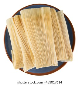 Tamales on blue plate, top down isolated.