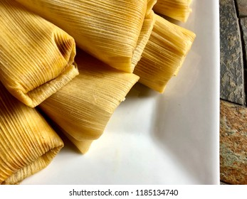 Tamales on a white plate, overhead view