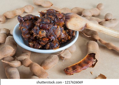 Tamarind pulp taken on a white plate surrounded by tamarind pods