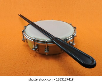 Tamborim and drumstick: a Brazilian percussion musical instrument. It is used to play samba, the famous Brazilian rhythm and has great prominence in the parades of samba schools, in the carnival.