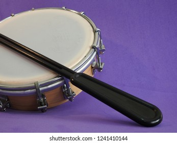 Tamborim and drumstick: a small, round Brazilian frame drum. It is widely used to accompany samba. It has great prominence in the parades of samba schools, in the Brazilian carnival.