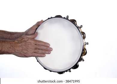 A tambourine being played by a man?s hands isolated against a white background.