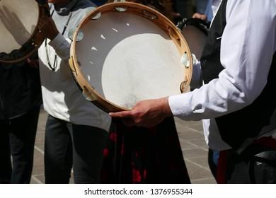 Tambourine playing pizzica music in the village piazza,Squalzino, Puglia, Italy