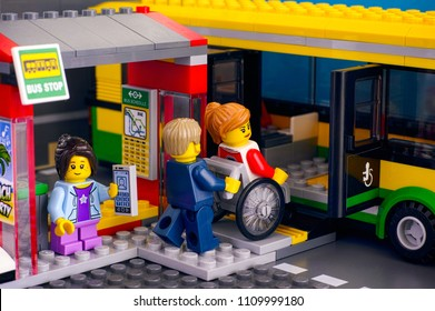 Tambov, Russian Federation - April 21, 2018 Lego Bus Station with bus and passenger - man helps woman in wheelchair, girl with smartphone. Studio shot.