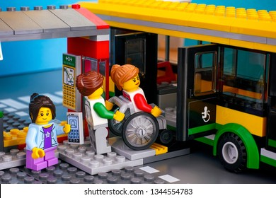 Tambov, Russian Federation - April 21, 2018 Lego Bus Station with bus and passenger - woman helping woman in wheelchair and girl with smartphone. Studio shot.