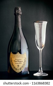 Tambov, Russian Federation - August 14, 2018 Bottle of Champagne Dom Perignon Vintage 2005 with wineglass against black background. Studio shot.