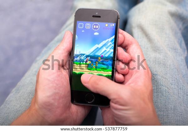 Tambov, Russian Federation - December 17, 2016 Man playing Super Mario Run game app on iPhone.