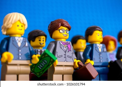 Tambov, Russian Federation - February 05, 2018 Lego businesswoman and businessman minifigures standing in rows. Blue background. Studio shot.