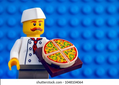 Tambov, Russian Federation - February 05, 2018 Lego chef with pizza against blue baseplate background. Studio shot.