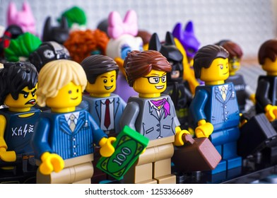 Tambov, Russian Federation - February 05, 2018 Lego minifigures. Lego businesswoman and businessmen standing in front row. Gray baseplate background. Studio shot.