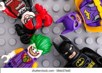 Tambov, Russian Federation - February 11, 2017 Four Lego Batman Movie minifigures - Batgirl, Batman, The Joker, Harley Quinn - on Lego gray baseplate background. Studio shot.