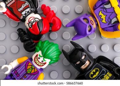 Tambov, Russian Federation - February 11, 2017 Four Lego Batman Movie minifigures - Batgirl, Batman, The Joker, Harley Quinn - on Lego gray baseplate background. Studio shot.